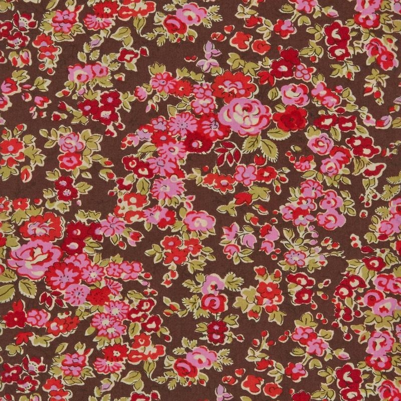 Liberty Tatum print on a brown background with pink flowers